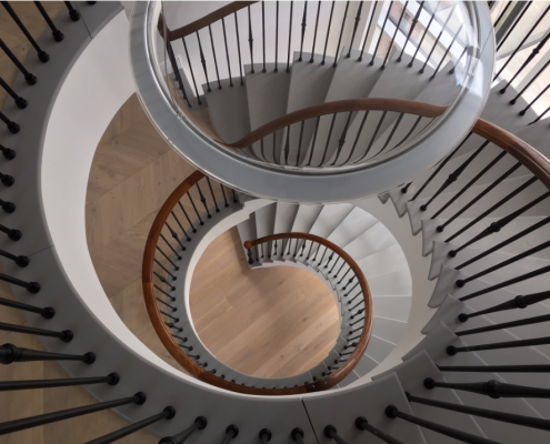 Spiral staircase with bespoke continuous Walnut handrail and steel balustrade