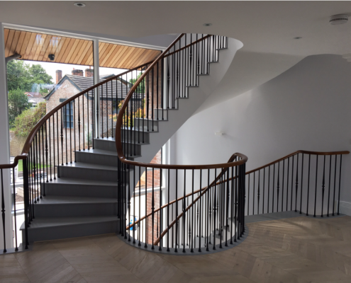 Spiral staircase with bespoke Walnut handrail and steel rounded spindles