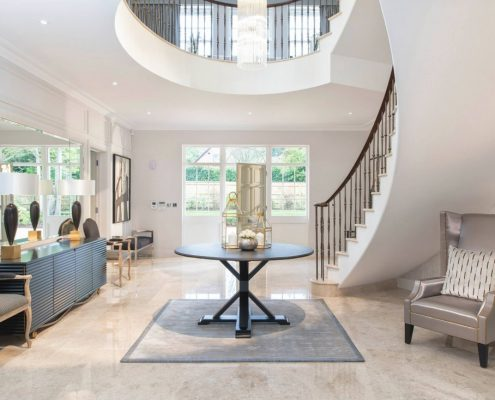 Curved stone staircase start with Walnut handrail & steel spindles