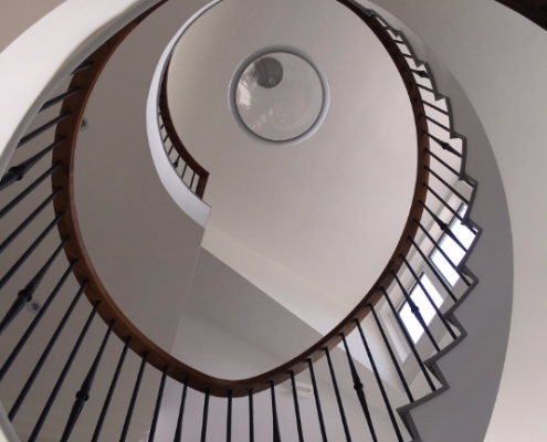 Sweeping spiral staircase with bespoke Walnut handrail and steel rounded spindles