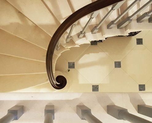 Monkey tail sat on post on stone stairway, Mahogany handrail