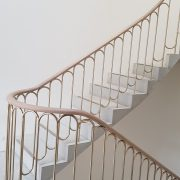 Cantilever stone stairs in art gallery, with brass balustrade and oak handrails