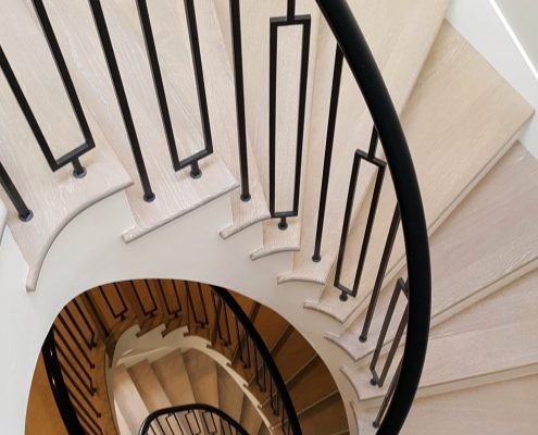 Downward view of spiral staircase on Little Boltons project with Piano black timber handrails & steel balustrade
