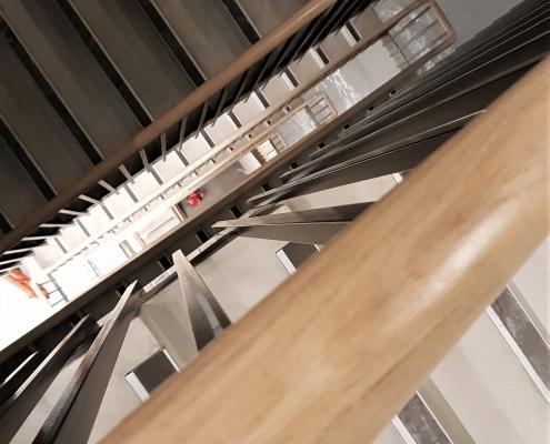 Hawk eye view of mopstick Oak handrails to numerous floors, continuous handrail