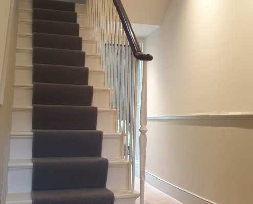 Mahogany handrail and White square profile spindles with fixed newel post on 1st tread