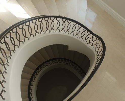 Curved staircase with curved handrail and bronze finished balustrade
