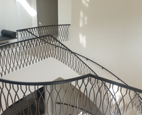 Landing view of timber handrail in Black with bronze finished steel balustrade