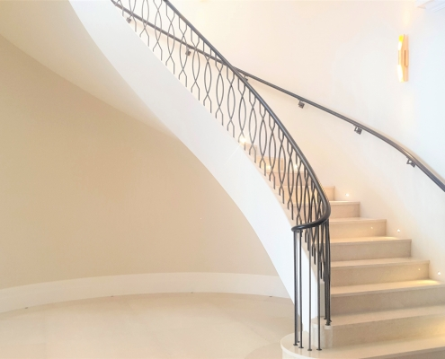 Ash handrails on curved staircase with LED spotlights near stair treads