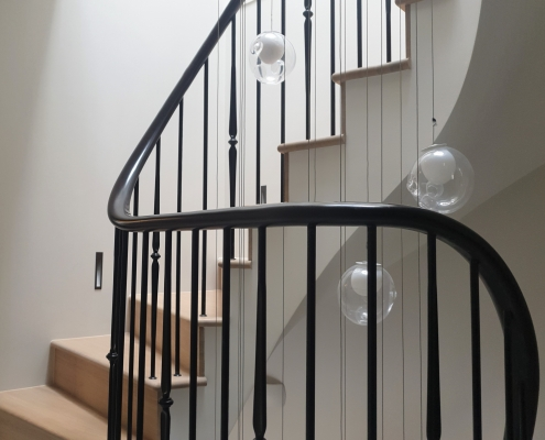 Curved bespoke timber handrail in Black with steel rounded spindles to treads