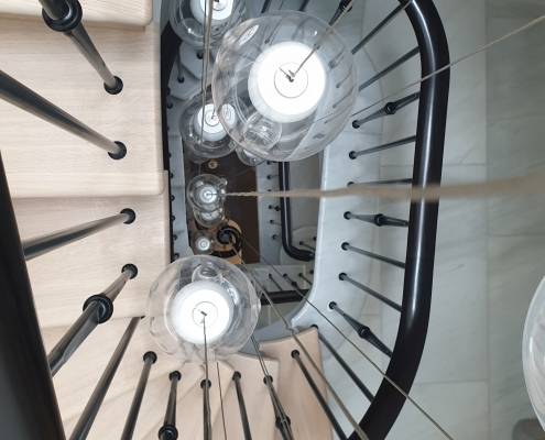 Hawk eye view of spiral staircase with Piano Black handrails and rounded spindles