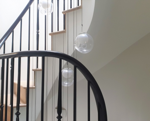 Helical & wreathing handrail sections with steel rounded spindles to stair treads