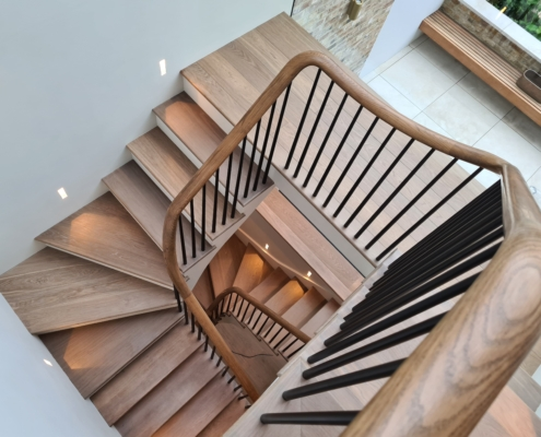 Hawk eye view of light timber handrails with Black rounded spindles to multiple floors