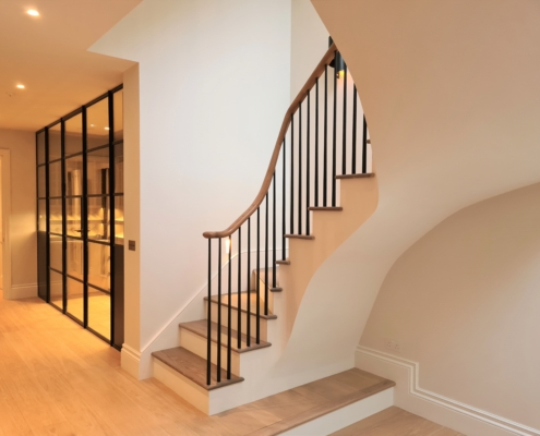 Rising curved Oak handrail with Black rounded spindles