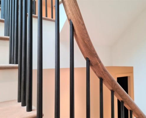 Tapered Black rounded spindles fixed to rising timber handrail