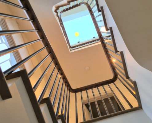 Upward view of rising handrails and Black rounded spindles to multiple floors