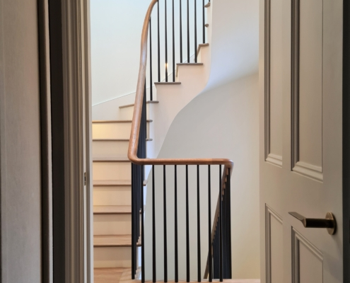Hallway staircase with curved and straight handrail runs and Black rounded spindles