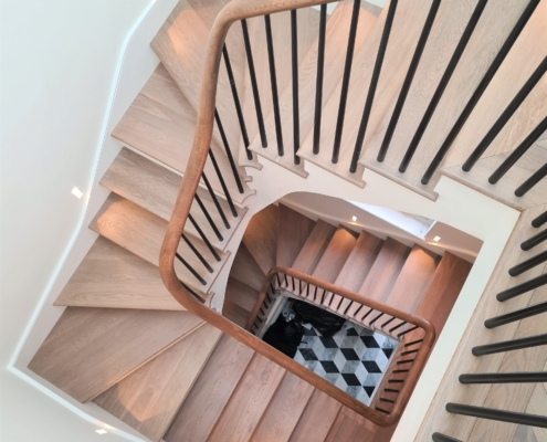 Hawkeye view of light timber bespoke curved handrails with Black rounded spindles
