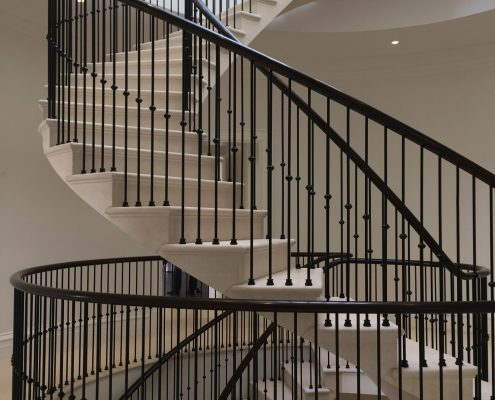 Continuous bespoke timber handrail & spindles to stone spiral staircase
