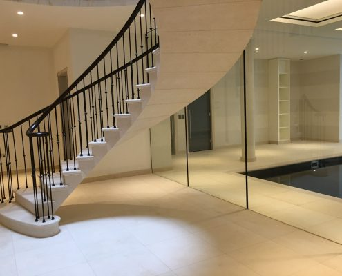 Stone curved staircase with Black matching coloured bespoke handrail & steel spindles