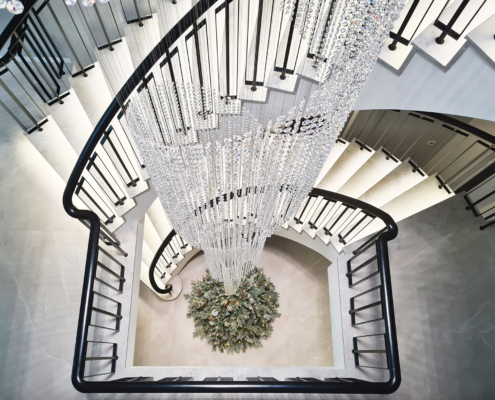 Curved stone staircase with Black balustrade and chandelier