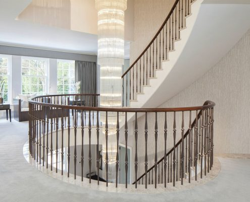 Landing view of Walnut continuous handrail and steel balustrade with central feature light