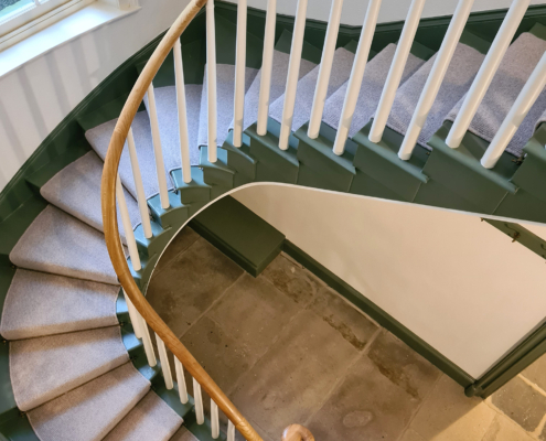 Curved oak staircase with rising handrail and White spindles