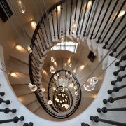 Mahogany handrails running down spiral stone staircase with floating light fittings
