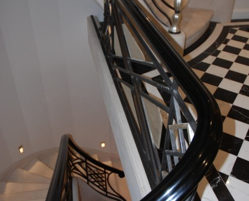 Wreathing section of stained finished handrail with steel balustrade on stone staircase