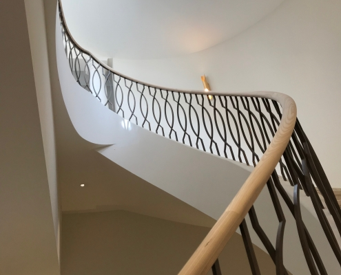 Spiral staircase with rising helical oak handrail sections