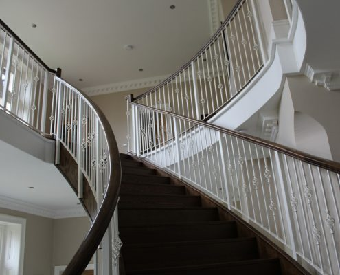 Curved staircase with bespoke timber handrail & steel spindles either side
