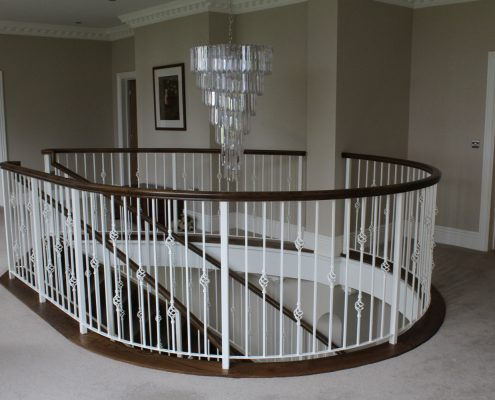 Landing shot of Oak curved handrail colour to match stair treads complete with steel balustrade in White