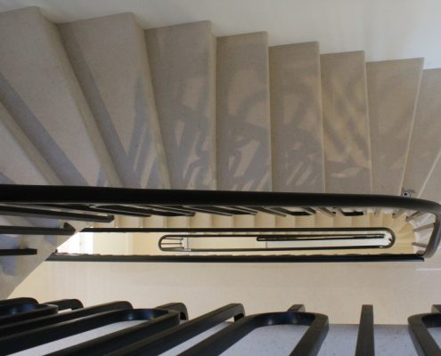 Hawkeye view of continuous oval handrail with a polished finish and steel balustrade