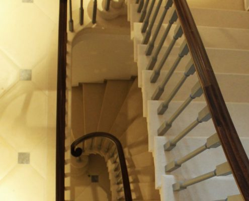 Downward view of stone stair with Mahogany handrails