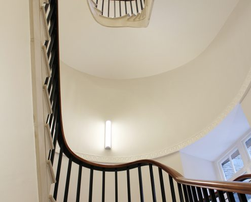 Dark toned bespoke timber handrail with Black steel balustrade to staircase