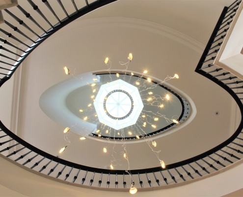 Curved staircase with matching coloured timber handrail & steel balustrade, drop down LED lights
