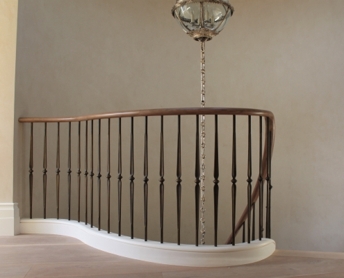 Landing section of curved Black Walnut handrail with steel brass finished balustrade