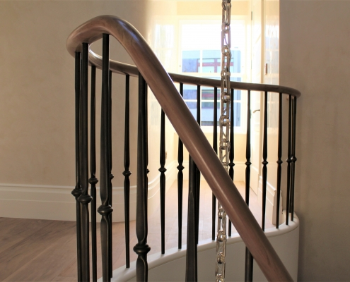 Helical section of bespoke dark toned handrail rising to landing