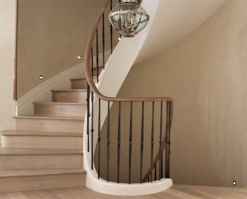 Helical oak handrail section rising up staircase and brass finished spindles