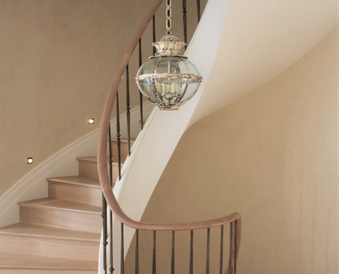 Helical section handrail from landing rising up staircase with steel brass finished spindles