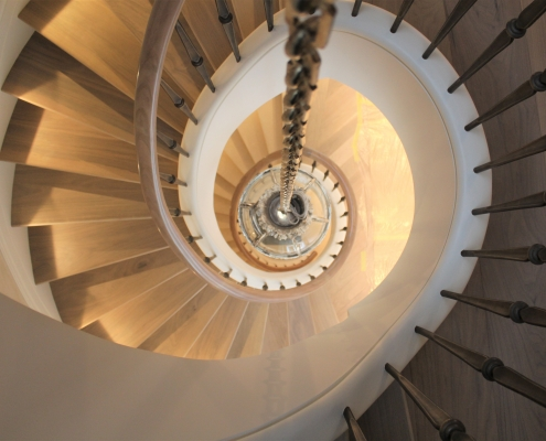 Spiralling staircase with bespoke helical handrails in Oak