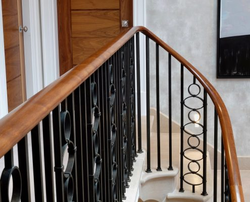 Walnut handrail with rising helical section to landing with steel square spindles