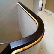Curved dark tone timber handrail on landing