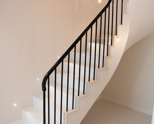 Sapele handrail with a French polished finish with steel rounded spindles on stone staircase