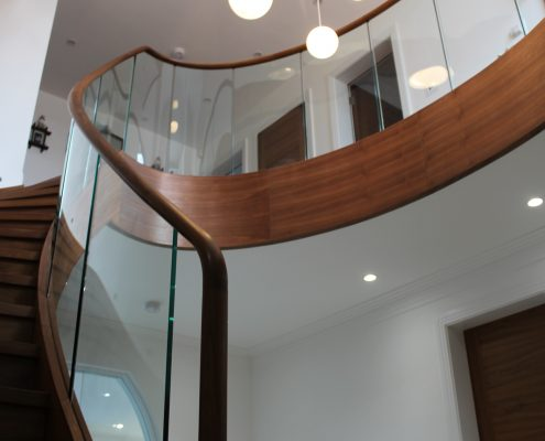 Walnut handrail with glass balustrade to timber staircase featuring Father Christmas!