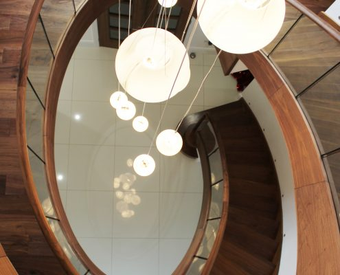 Hawk eye view of spiral staircase with Walnut timber handrails and glass balustrade