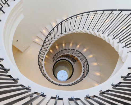 Continuous handrail leather wrapped with steel balustrade to spiral stone staircase