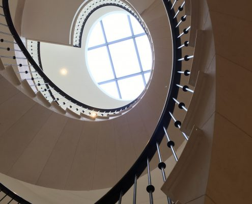 Spiral stone staircase with bespoke timber handrail and steel Black spindles