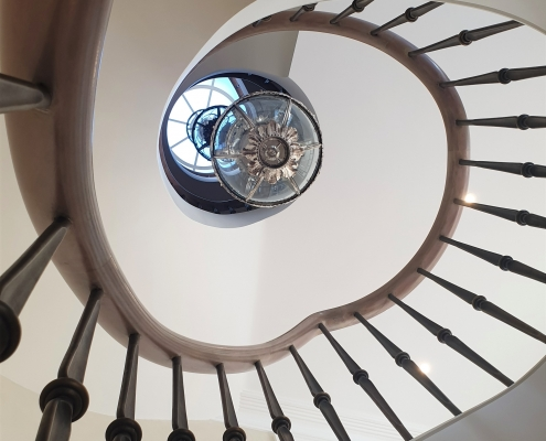 Rising bespoke dark toned timber handrail with Steel balustrade to curved staircase