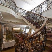 Helical Ash timber handrail and steel balustrade to curved staircase in a restaurant