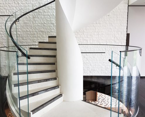 Spiral staircase with glass balustrade and Black timber helical rising handrails